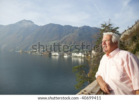 The senior man enjoy his travel by the lake of Switzerland. - stock photo