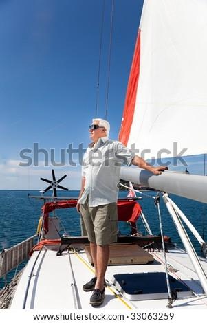 The senior man enjoy his vacation on the sailboat. - stock photo