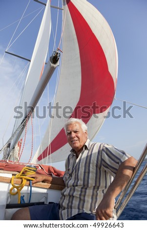 The senior man enjoy the gentle sailing in the summer. - stock photo