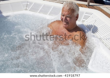 The senior man enjoy the outdoor jacuzzi in the sun. - stock photo