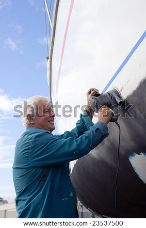 The senior man happy working on the side of a sailboat. - stock photo