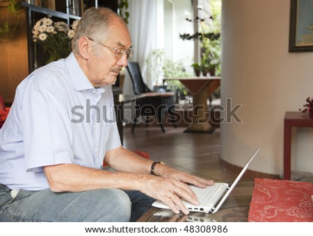 The senior man uses his laptop in the living room. - stock photo
