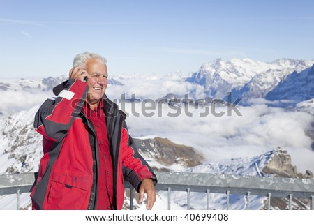 The senior man uses his mobile to communicate on the high mountains. - stock photo