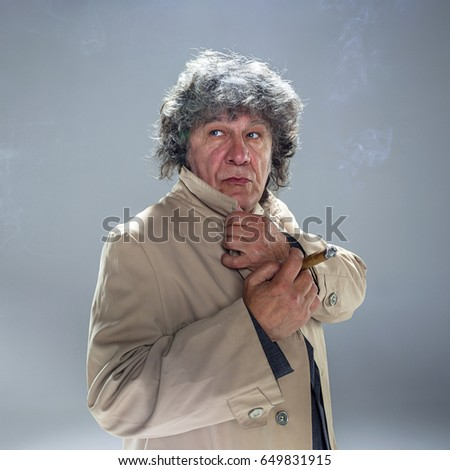 The senior man with cigar as detective or boss of mafia on gray studio background