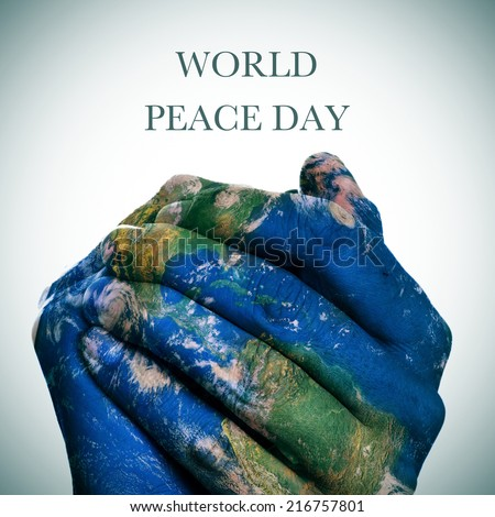 the sentence world peace day  and a world map in man hands forming a globe (Earth map furnished by NASA) - stock photo