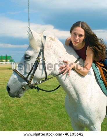 The serenity young girl astride a horse against blue sky - stock photo