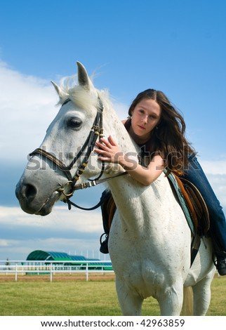The serenity young girl astride a horse against blue sky. Shallow DOF - stock photo