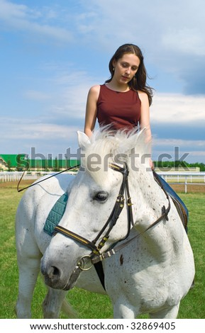 The serenity young girl astride a horse against blue sky. Shallow DOF, focus on a face of girl - stock photo