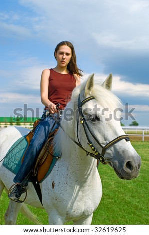 The serenity young girl astride a horse against blue sky. Shallow DOF, focus on a muzzle of a horse - stock photo