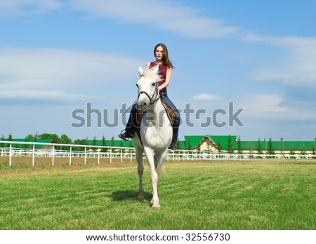 The serenity young girl astride a horse on a hippodrome - stock photo