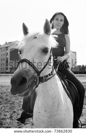 The serenity young girl astride a horse. Shallow DOF, focus on horse - stock photo