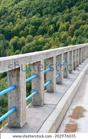The series of concrete columns, reinforced with blue pipes, as a bridge guard rail. Landscape with forest and concrete bridge - stock photo