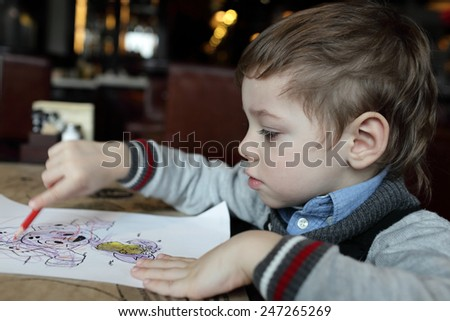 The serious boy drawing at the cafe - stock photo