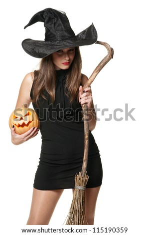 The  serious brunette witch with a broom and pumpkin - stock photo