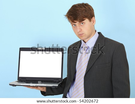 The serious businessman holds on a hand the laptop on a blue background