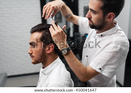 the serious client is sitting in the salon and professional hairstylist is cutting the clients hair - Professional Hair Stylist