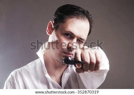 The serious man with the pistol in a white shirt