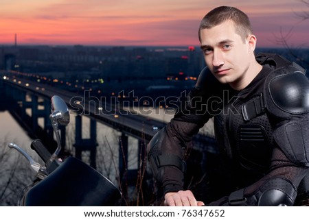 The serious Motorcyclist and its motorcycle against an evening city, the river and the bridge through the river.