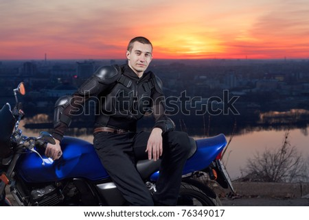 The serious Motorcyclist and its motorcycle against an evening city, the river and the bridge through the river. - stock photo