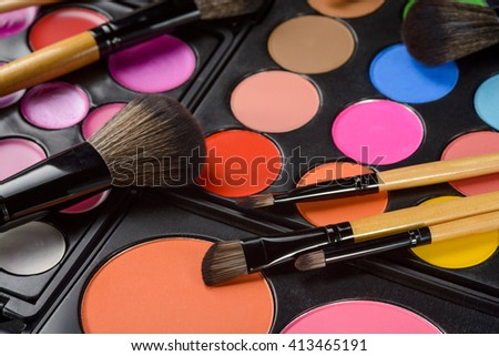 The set for make-up consists of the complex of palettes with cosmetics of different usage: for eyes, lips and skin. Scattered brushes for separate facial zones. Bright colors for cool mood. - stock photo