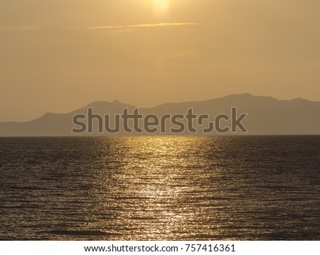 The setting sun cast highlights in the ocean and over the mountains near Ko Chang island, Thailand