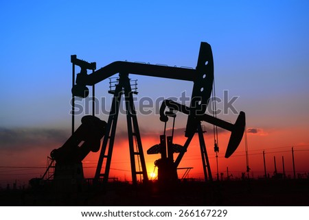 The setting sun is operation of the pumping unit in oil field  - stock photo
