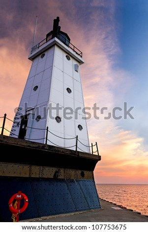 The setting sun provides a dramatically colorful backdrop to the metal-clad Ludington North Breakwater Lighthouse in Ludington, Michigan. - stock photo