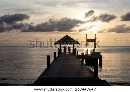 The setting sun silhouettes a pier overlooking Palau's western lagoon. This tropical Pacific destination is popular among kayakers, scuba divers and snorkelers worldwide. - stock photo