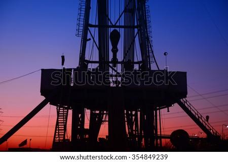 The setting sun under the oil derrick  - stock photo