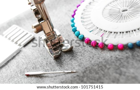 The sewing machine and needles on a fabric. - stock photo