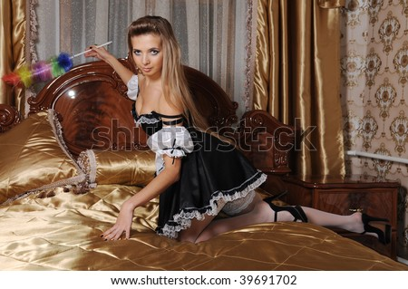 The sexual girl in a costume of the servant cleans a luxury room - stock photo