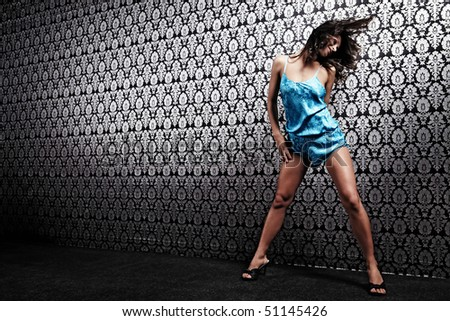 The sexual girl stirs up hair against a wall with a pattern