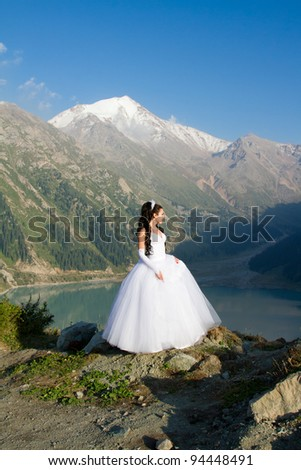 The sexy russian beautiful woman the bride in a wedding dress on mountain - stock photo