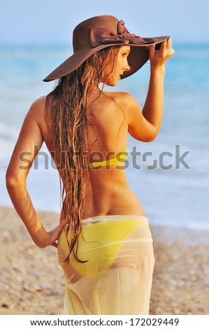 The sexy woman in yellow bikini and a hat having good time on a tropical beach - stock photo