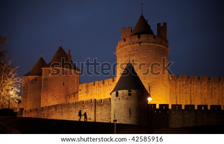 The shadow of a couple walkinkg by the carcassonne castle. - stock photo