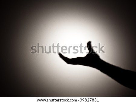 The shadow of a male hand against an illuminated white background - stock photo