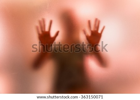 The shadow of a woman pretending to push or defend behind a frosted red glass - stock photo