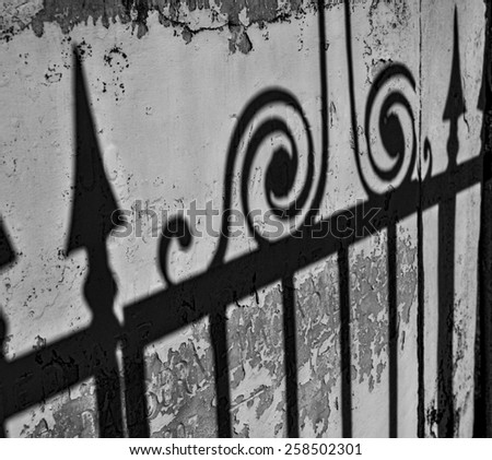 The shadow of an elaborate wrought iron fence on an old wall in New Orleans. - stock photo