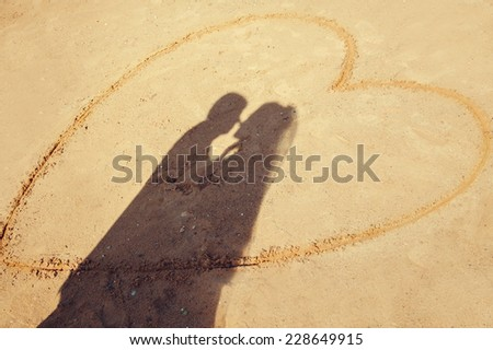 The shadow of two embracing lovers - the groom and the bride on the yellow sand of the beach encircled with a big heart. - stock photo