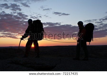 The sheaf of two climbers goes against decline - stock photo