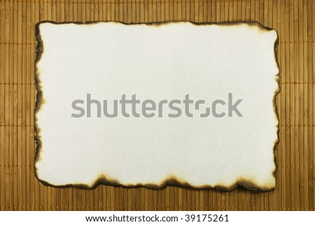 The sheet of an old paper with burnt edges lays on a bamboo laying