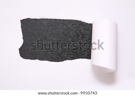 the sheet of torn paper against the black background - stock photo