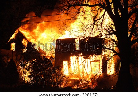the shell of tow houses burning uncontrollable in the night - stock photo