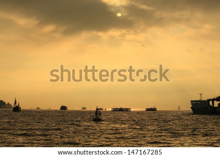 the ship cross the sea in the busy victoria harbour in evening sunset, crepuscular rays, and sun hide in the clouds in Hong Kong - stock photo
