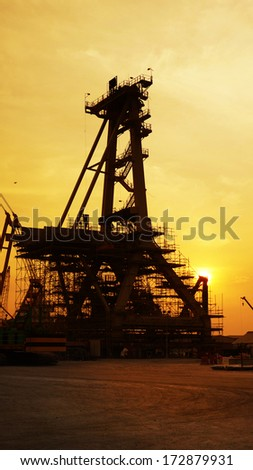 The Ship-loader Crane and structure silhouetted against sunset in construction oil & gas industries project. - stock photo