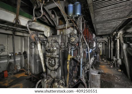 The ship's hold with diesel engine mounted on ship. Engine room on a old cargo boat ship. Focus on  the center of frame
