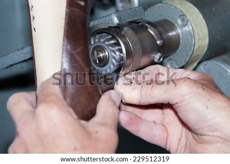 the shoemaker repairs a shoe - stock photo
