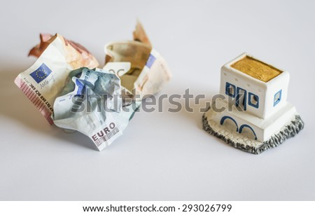 The shot is topical as it represents Greece debt crisis by banknotes and a typical Greek little house. The crumpled banknotes are Greek money crunch and the possibility Greece goes out of Euro zone  - stock photo
