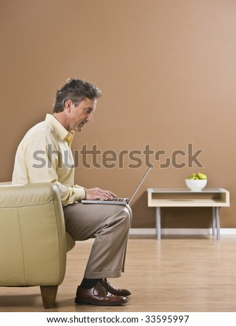 The side view of an attractive business man using a laptop.  He is seated on a sofa.  Vertically framed shot.