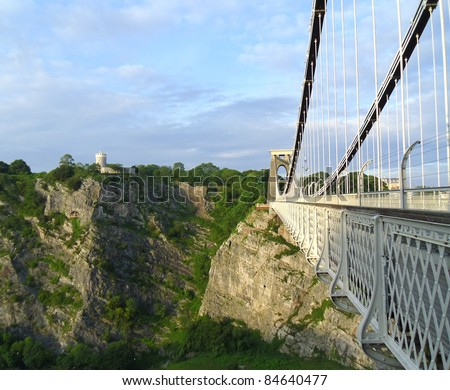 the side view of clifton suspension bridge with a viewpoint on the cliff in the background - stock photo